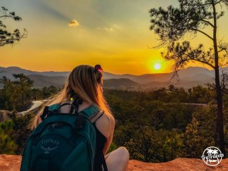 Girl sat on rock with backpack looking out to sunset