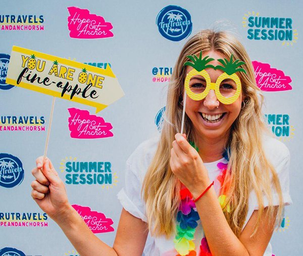 Girl holding pineapple glasses to face holding yellow sign with TruTravels summer party backdrop