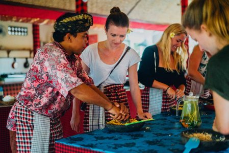 Balinese man teaching girl in cooking class wearing red aprons and blue table