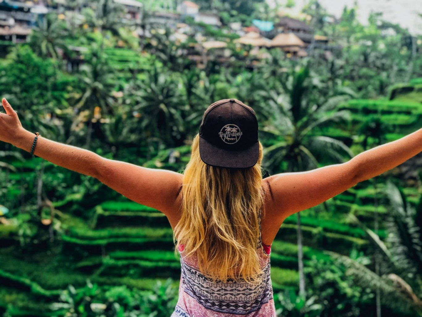 A girl posing with her arms out admiring the view of the emerald green rice terraces in Ubud, Bali, Indonesia