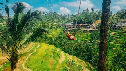 Girl on Bali swing surrounded with jungles and rices terraces
