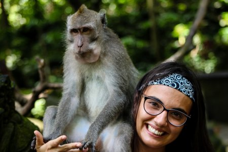 Girl smiling with monkey on her shoulder