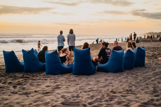 people sat in a circle of blue beach bean bags with sea behind