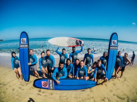 Large group  wearing blue wet suits with blue surf boards on sandy beach with sea in the background