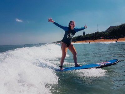 girl on surf board riding wave with arms open