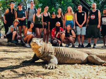 komodo dragon with group of travellers behind