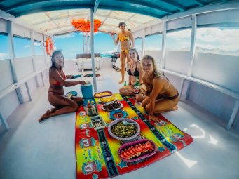 Girls sat around platter of food on boat