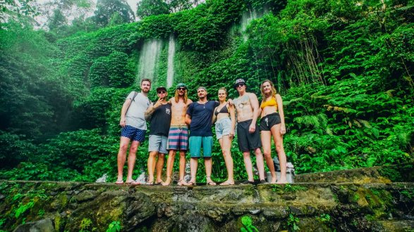 Group of travellers stood in front of waterfalls surrounded by green trees