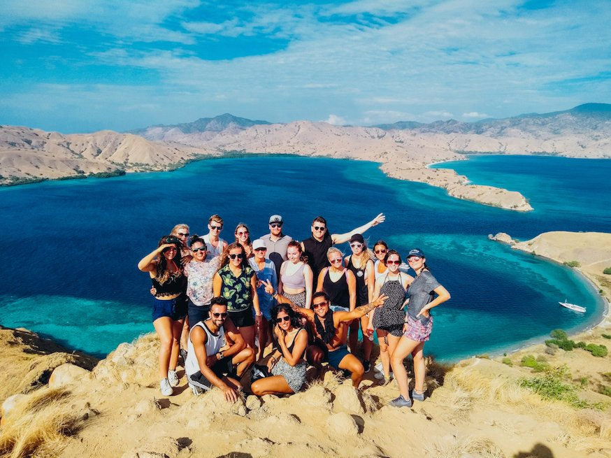 Group of travellers standing at the top of Padar view point with blur sea and hills in background