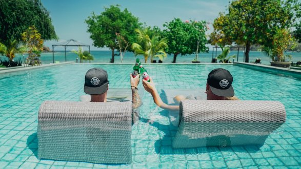 two men sat in pool bed with black hats on cheersing with beers