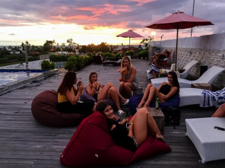 group of girls sat on decking by rooftop pool with pink sunset in the background