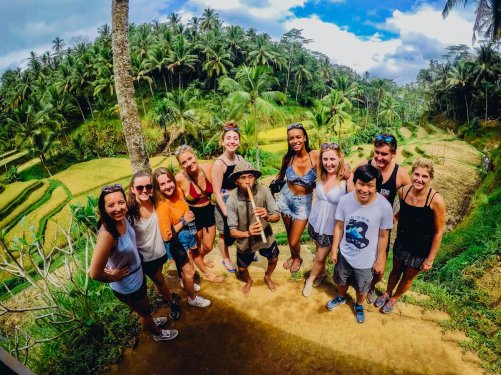 Group of travellers at Ubud rice terraces smiling with green trees in background
