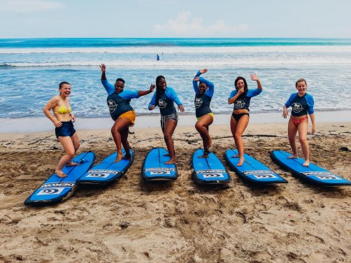 A group practicing their moves on their surf boards before heading into water for a lesson at Kuta beach Bali