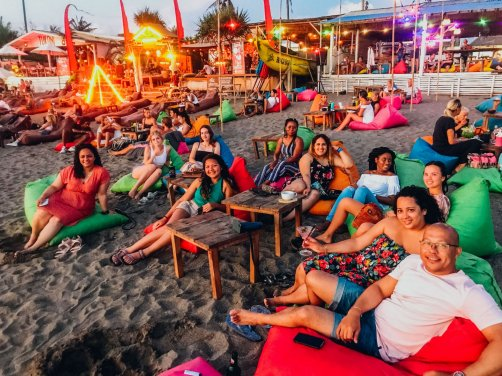 A group chilling on beanbags at the beach in Canggu, Bali, Indonesia