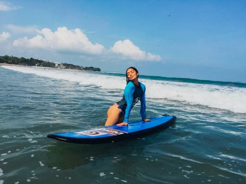 A girl in the sea with her surfboard on Kuta beach Bali Indonesia