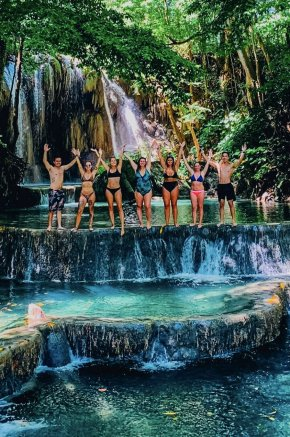 A group standing at the edge of a waterfall tier, showing crystal clear blue waters at Moyo Island, Indonesia