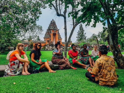 A group at the temple Taman Ayun, sat on the grass in Bali, Indonesia
