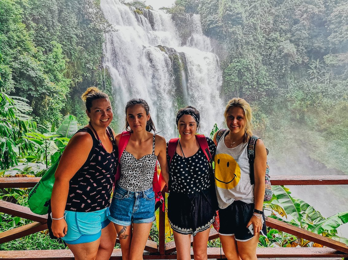 Four girls stood smiling in colourful shorts and t-shirts with waterfall behind