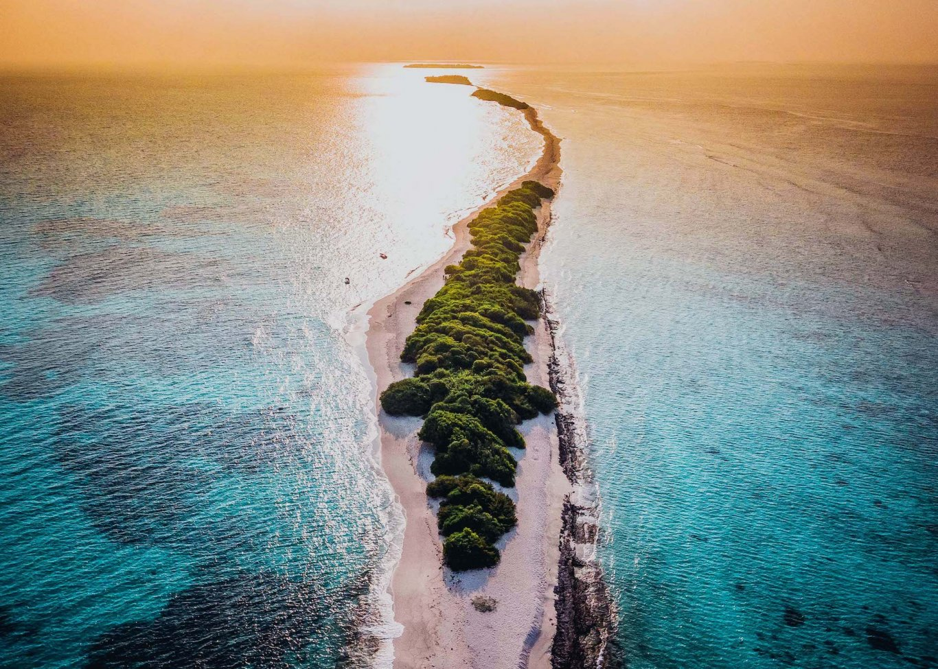 A long sandbank surrounded by bright blue water at sunset in the Maldives