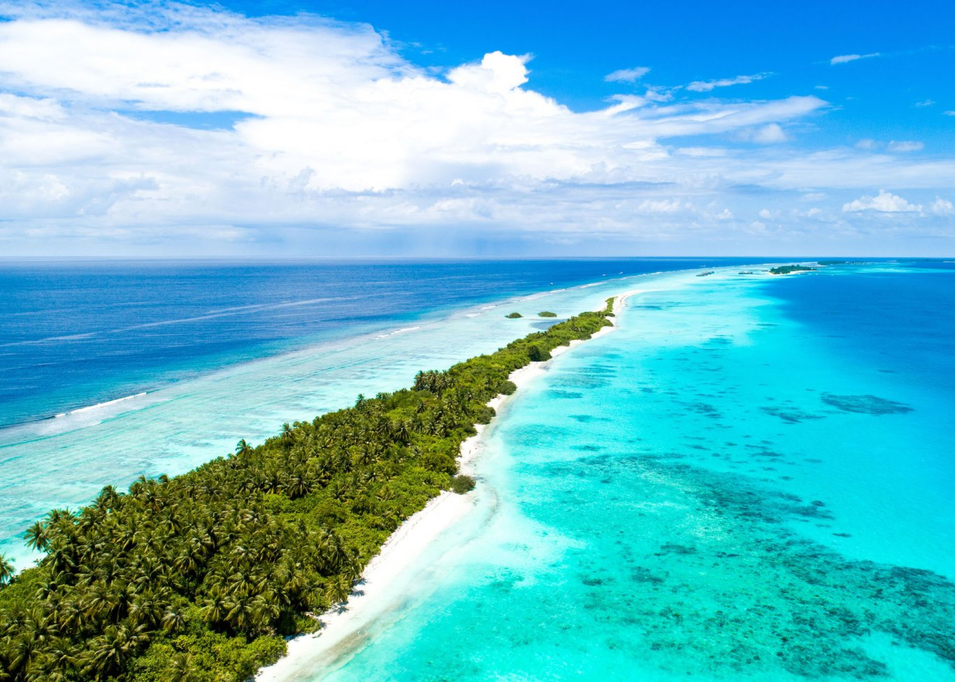A picturesque photo of a long stretch of a sandbank surrounded by lush greenery and bright blue turquoise water with coral reefs in view
