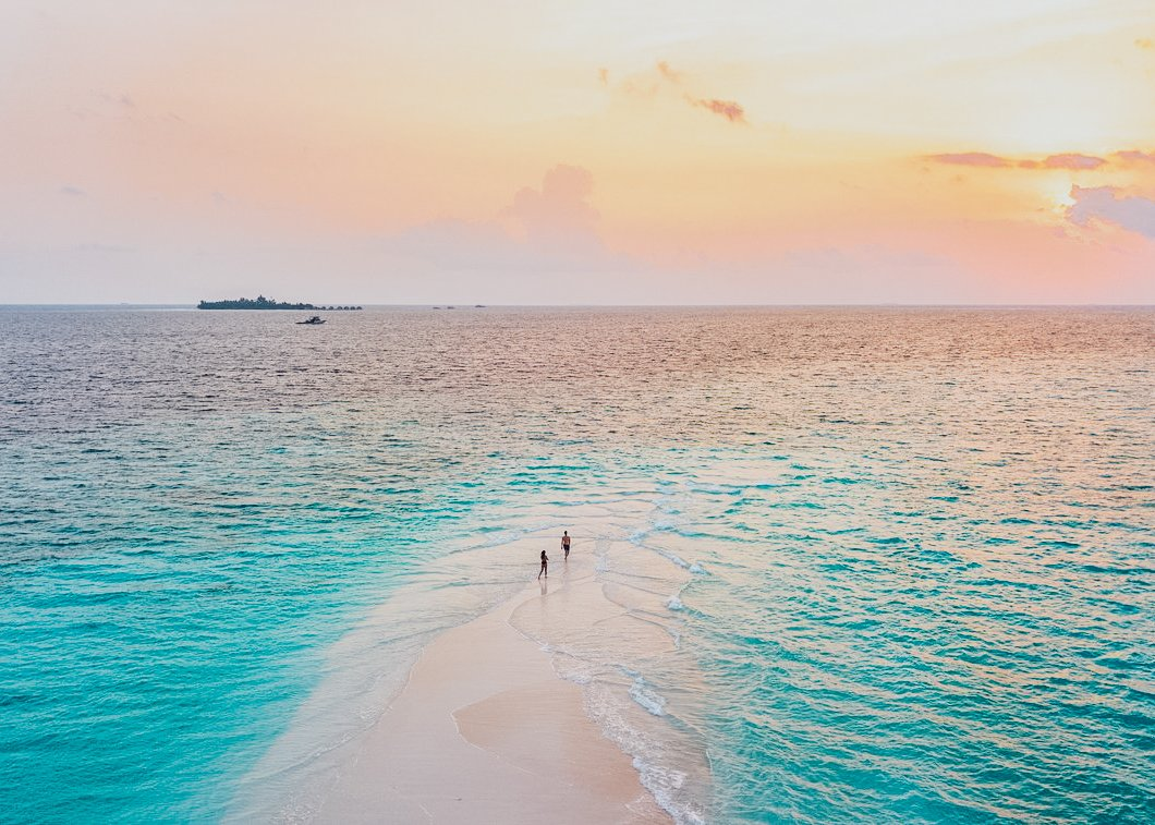 A shot of a small sandbank in the middle of the the bright blue clear ocean during a stunning orange and pink sunset in the Maldives