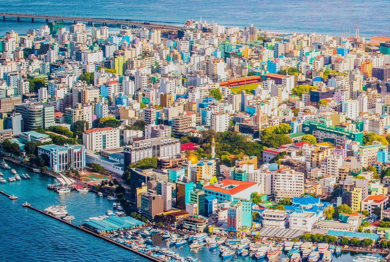 A drone shot of the capital city Male, in the Maldives showing different coloured buildings and the harbour in view.