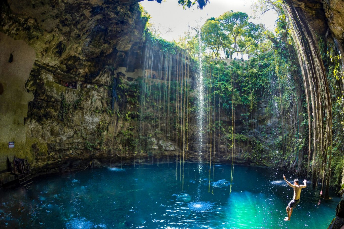 Mexican Cenote - blue water surrounded by limestone rock with man mid air jumping in the water