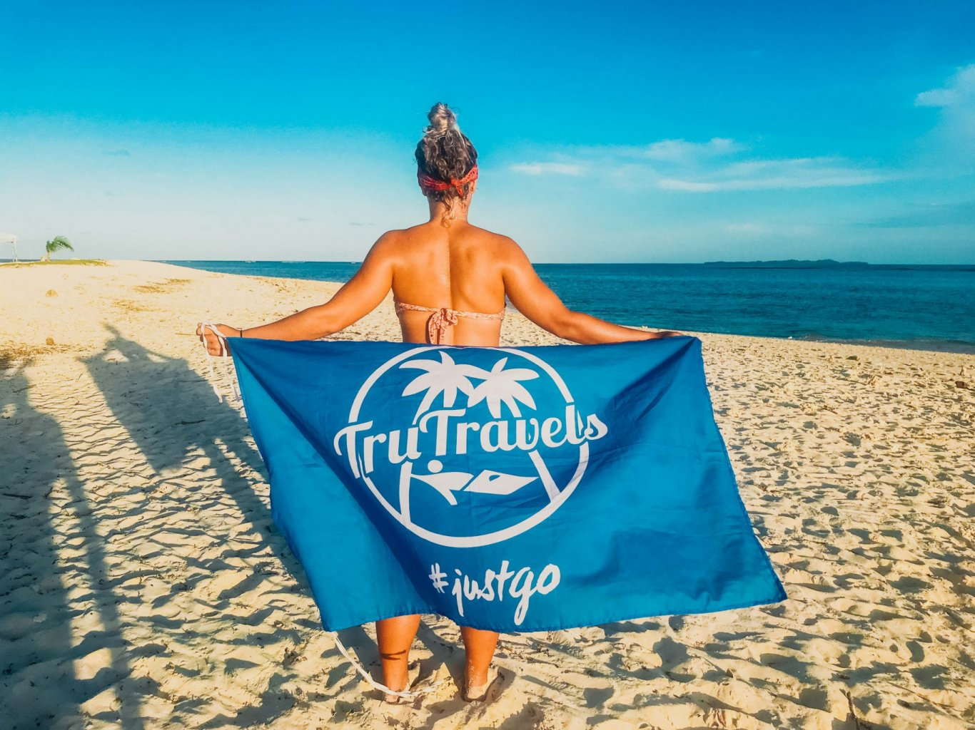 Girl on beach with TruTravels flag - Philippines