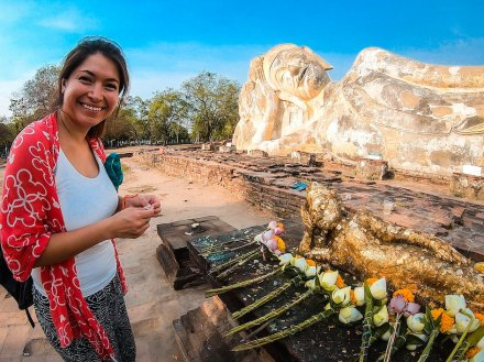 Girl standing in front of some flower offerings laid down next to a giant reclining buddha in ayutthaya, Thailand