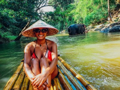 A girl on a bamboo raft trip with an elephant in the background bathing in the river in Chiang Mai Thailand