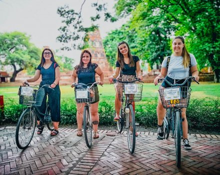 Four girls sitting on bikes with basket on the front with temples faintly showing in the background and green trees behind them