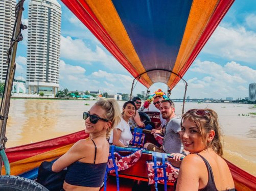 Group on a colourful long tail boat ride on Chao Phraya River