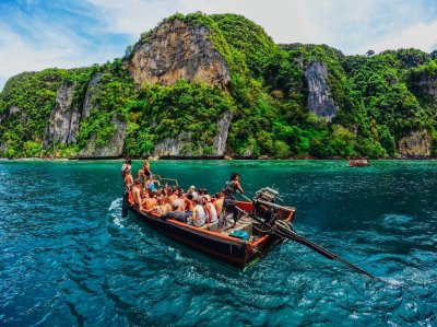 Group of people on a small boat sailing through deep blue waters and islands covered in trees surrounding them