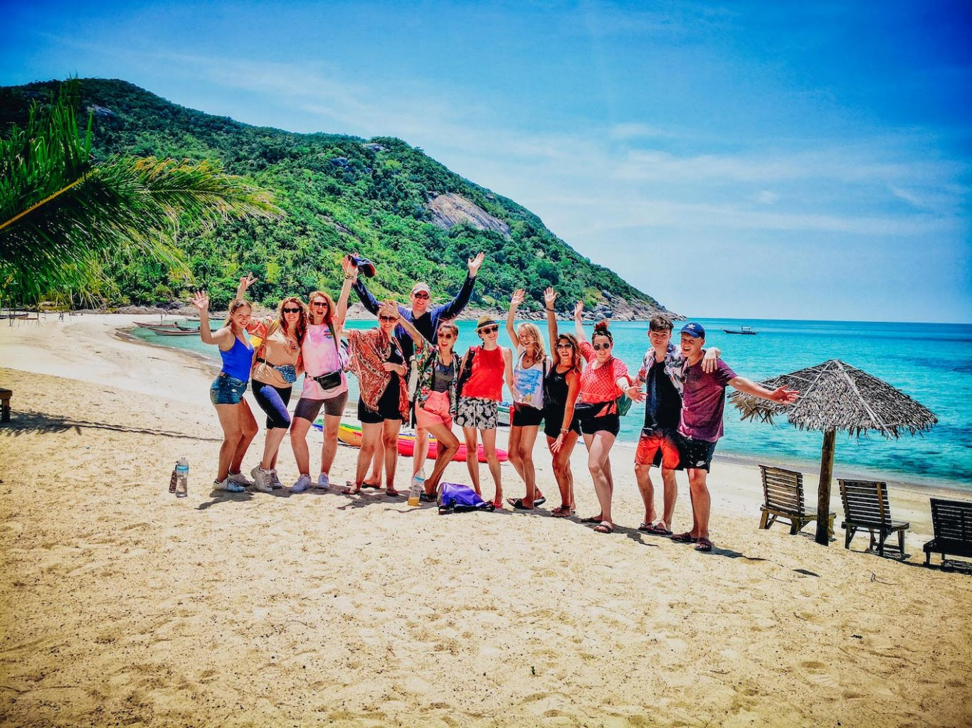 A group in front of the crystal clear blue water at bottle beach Koh Phangan