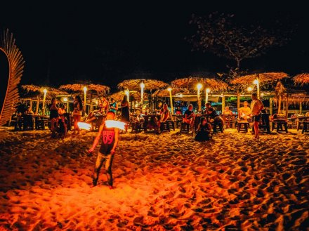 Fireshow on bottle beach in Thailand and people having drinks at tables in the background
