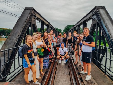 large group standing on bridge over the river kwai on a cloudy day in Thailand