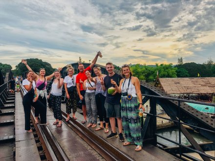 Group standing on the bridge over the river Kwai in Kanchanaburi Thailand