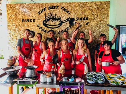 A group photo at the cooking class in Chiang Mai holding all the cooking utensils