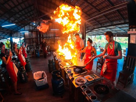 A group experimenting with flames in the wok at a cooking class in Chiang Mai Thailand