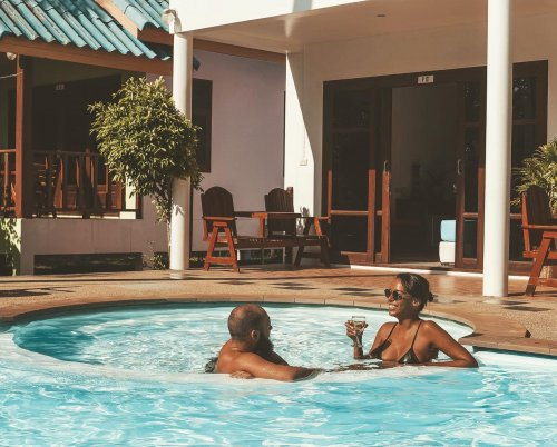 Couple relaxing in pool having a drink and laughing together at hotel in Thailand