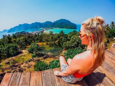 Girl sitting at Koh Phi Phi Thailand Viewpoint overlooking ocean and lush green Palm Trees