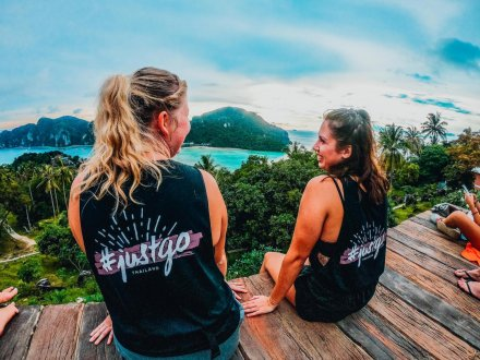 Two girls wearing TruTravels vests sitting at viewpoint in PhiPhi, Thailand with the ocean and islands in front of them