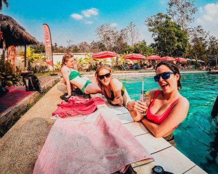 3 girls chilling by a pool in Thailand having drinks