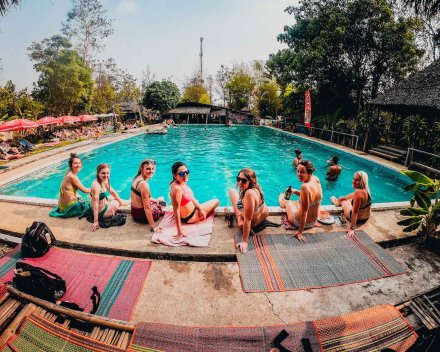 girls in bikinis sat by large pool in Thailand