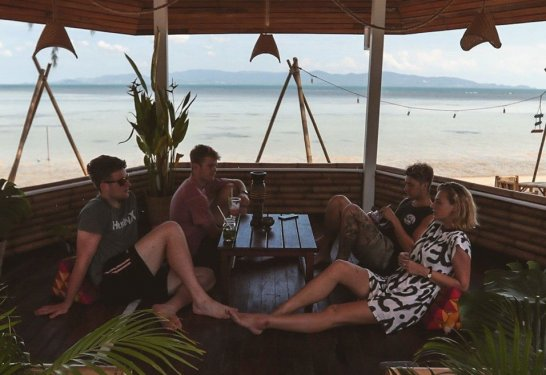 Group of friends sitting enjoying a drink at beach bar overlooking the ocean on the beach
