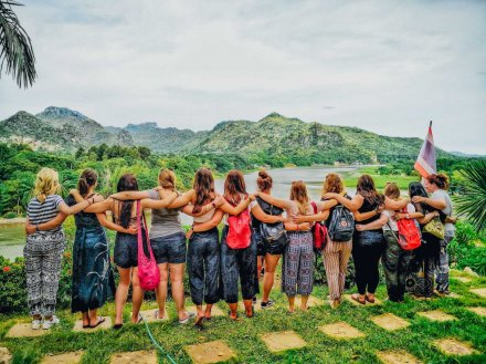 Group of girls with arms round each other facing a viewpoint in Kanchanaburi in Thailand