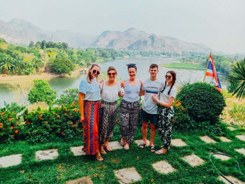 group of young people standing with beautiful scenery of lakes and mountains in the background in Thailand