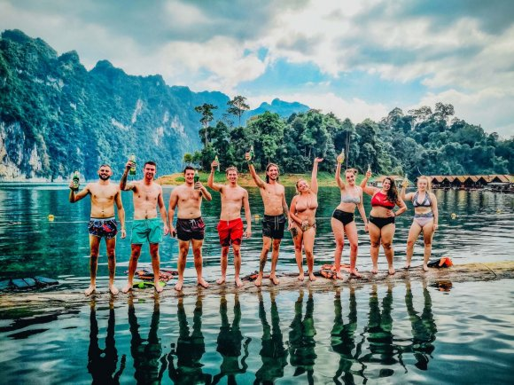 A group photo on a log in the water at Khao Sok national park Thailand