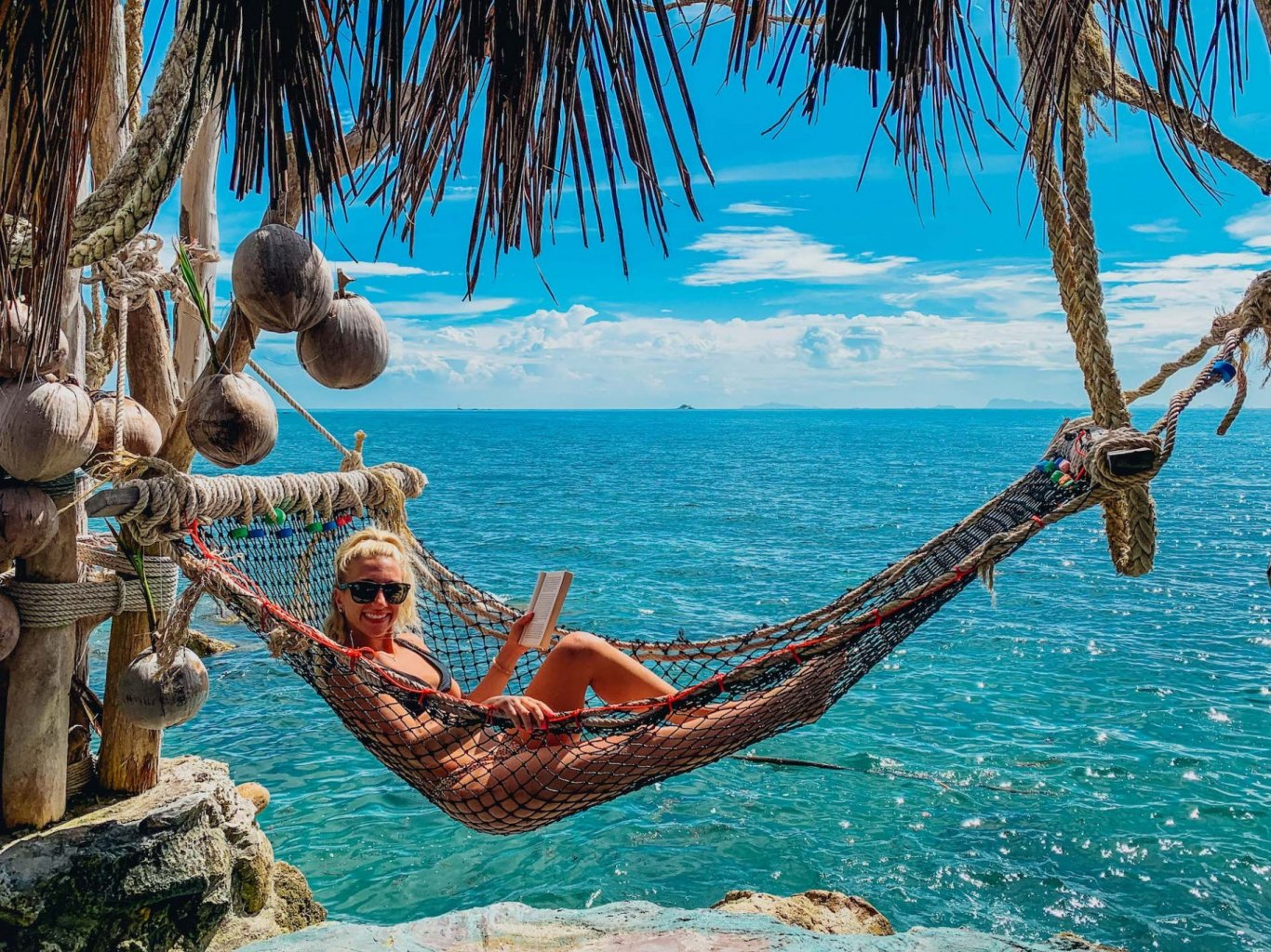 A picturesque photo of a girl on a hammock by crystal clear blue waters in Koh Phangan Thailand