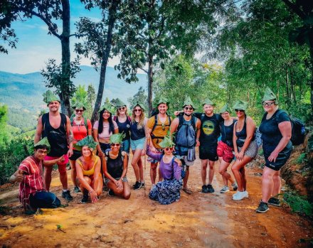 A group hiking in Chiang Mai Thailand wearing hats made out of banana leaves